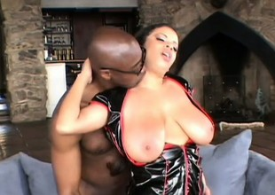 Busty as fuck tart in a vinyl corset gets filled with a coloured dick