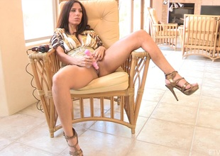 Cougar in high heels pleases her muff with a vibrator on a chair