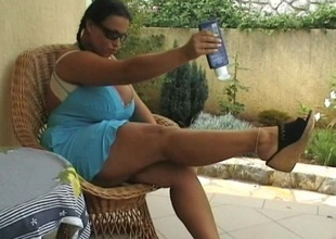 Brunette honey outside on the grass massaging her big bra buddies