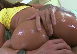 Sexy ass is getting smeared with oil and then placed in front of us