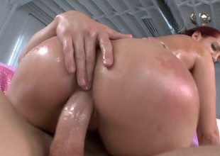 Redhead has a lot of oil on her body to make her more slippery