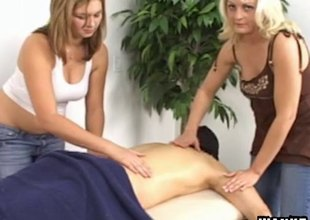 Lucky dude gets a massage and a blowjob from two hussies
