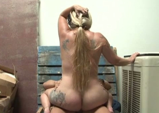 Chubby tattooed and large breasted golden-haired whore is fucked in warehouse