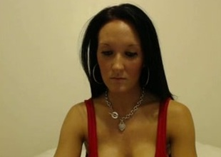 Slender brunette milf demonstrates her fake tits in webcam chat