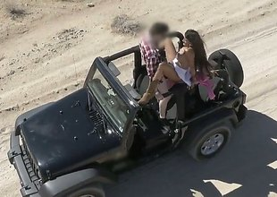 Breasty Mercedes Carrera gets in a jeep and takes off her top. She then gets driven around the beach with the hot sun tanning her constricted body. She then humps the driver.
