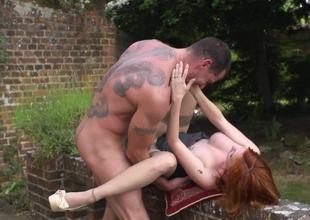 Redhead is outside, in the garden, receiving a big dick in her