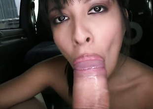 Brunette engulfing dick in a car