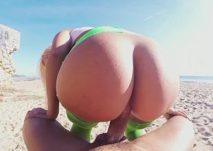 Blonde with sizable boobs and a massive ass fucks on the beach